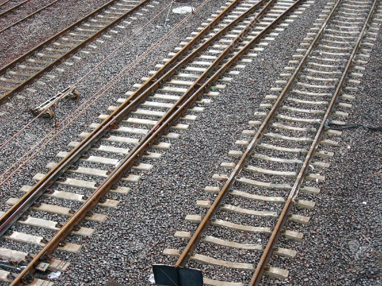 3533720-Parallel-lines-of-rusted-railway-tracks-set-in-grey-moisty-clinker--Stock-Photo